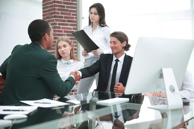 Partner biznesowy uścisnąć dłoń na spotkaniu w nowoczesnym budynku biurowym. koncepcja biznesowa