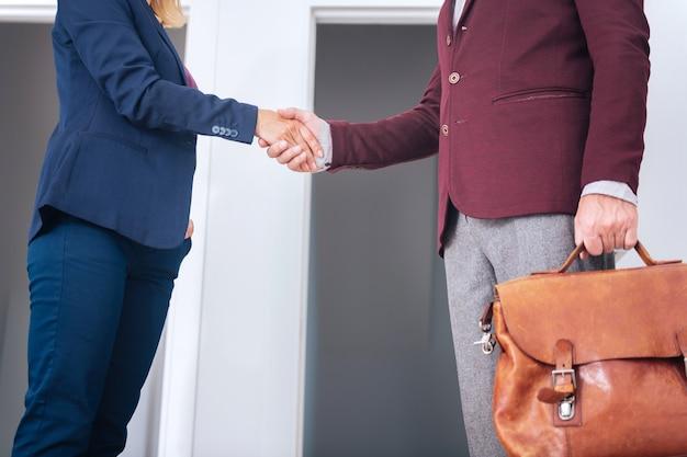 Partnerka. dojrzały biznesmen ubrany w szare spodnie ściskając rękę swojej przyszłej partnerki po ważnych negocjacjach