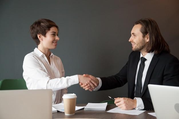 Partnerów biznesowych powitanie z uściskiem dłoni podczas biurowego spotkania