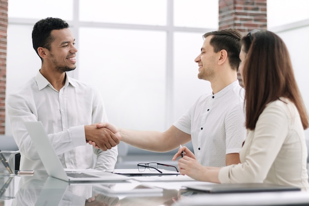 Partnerów biznesowych uzgadniania siedzi w biurze desk.