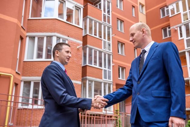 Partnerów biznesowych uzgadnianie przed dużym budynkiem na zewnątrz