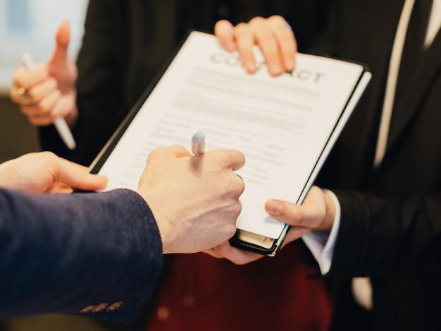 Partnerstwo i współpraca. umowa biznesowa. relacja korporacyjna. zbliżenie ręki człowieka podpisywania umowy.