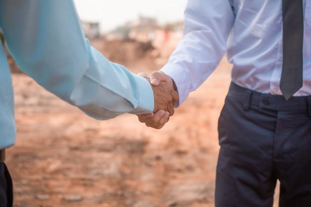 Partnerstwo kontrahenta uścisnąć dłoń na budowie