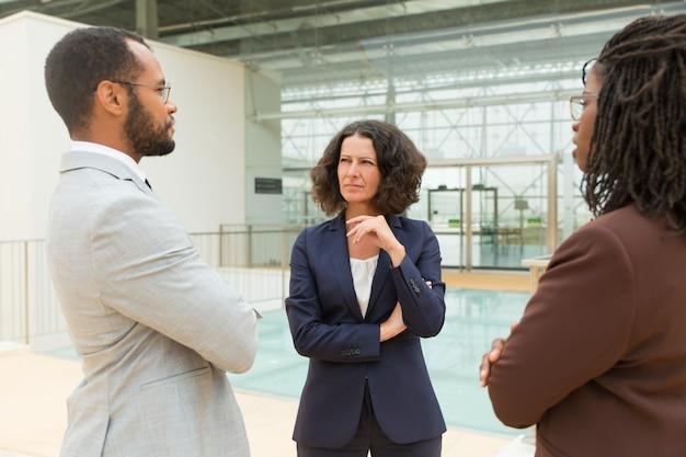 Partnery biznesowi dyskutuje projekt w biurowym korytarzu