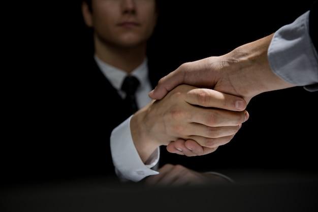 Partnery biznesowi robią uścisk dłoni w ciemnym cieniu