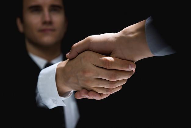 Partnery biznesowi robią uścisk dłoni w cieniu
