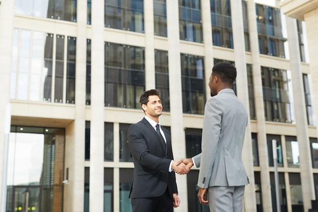 Partnerzy biznesowi drżenie rąk na zewnątrz