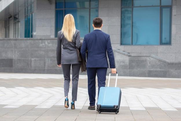Partnerzy biznesowi, mężczyzna i kobieta, chodzą razem i prowadzą dialog