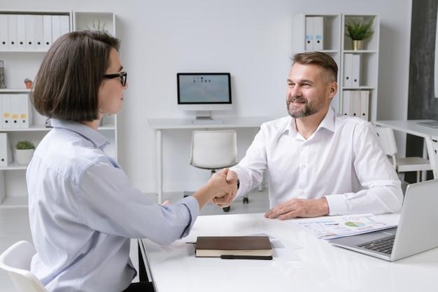 Partnerzy biznesowi odnoszący sukcesy uścisk dłoni po podpisaniu nowej umowy i zawarciu umowy na spotkaniu