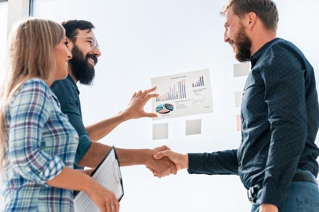 Partnerzy biznesowi omawiają zyski na wykresie finansowym