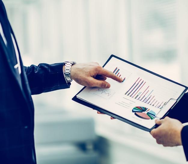 Partnerzy biznesowi omawiający wykresy finansowe przyszłej umowy