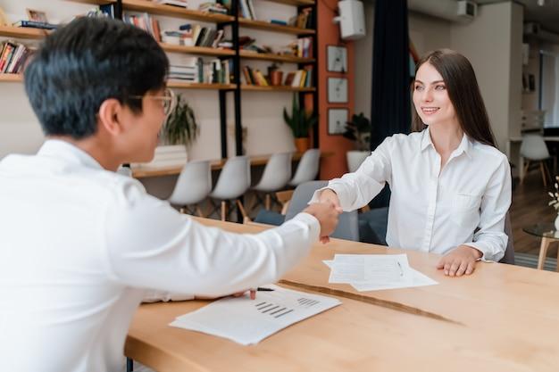 Partnerzy biznesowi podają sobie ręce i podpisują dokumenty w biurze