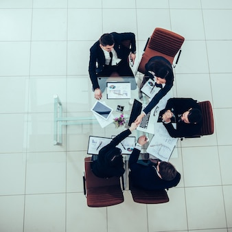 Partnerzy biznesowi podają sobie ręce po dyskusji na temat nowego f