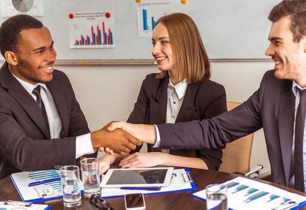 Partnerzy biznesowi podają sobie ręce w biurze.