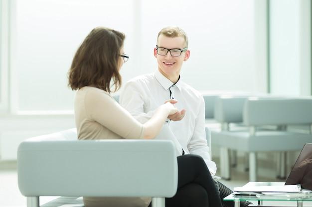 Partnerzy biznesowi, ściskając ręce, siedząc w biurze banku. koncepcja współpracy