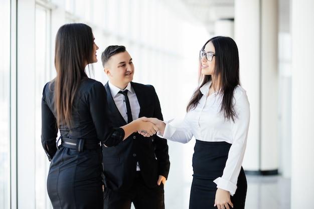 Partnerzy biznesowi, ściskając ręce w sali konferencyjnej. dwa biznes kobieta pozdrowienia uścisk dłoni w biurze