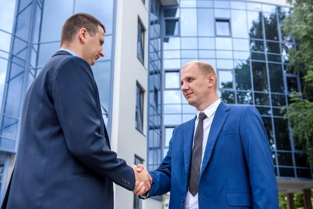 Partnerzy biznesowi uścisk dłoni w pobliżu biurowca na zewnątrz