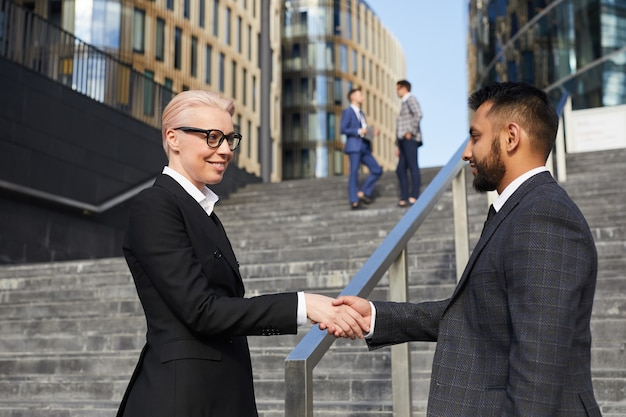 Partnerzy biznesowi uścisk dłoni witają się w mieście