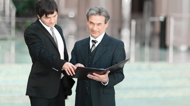 Partnerzy biznesowi z dokumentami stojącymi w biurze.zdjęcie z miejscem na kopię