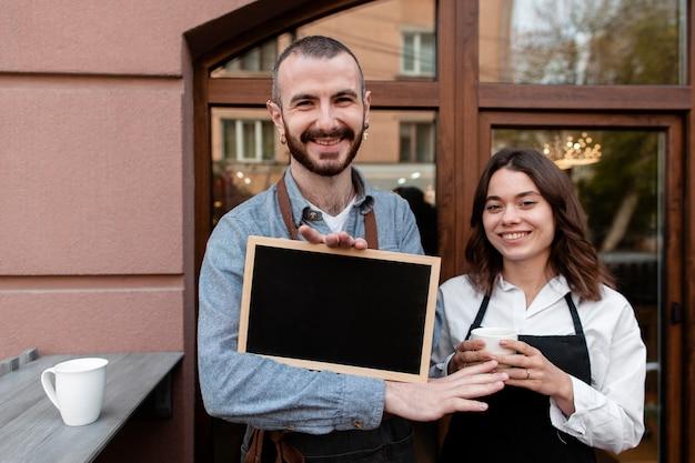 Partnerzy biznesowi z ramą przy sklep z kawą