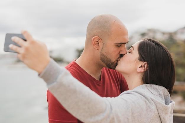 Partnerzy całują się podczas robienia selfie