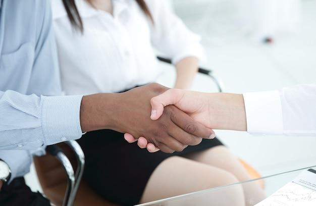 Partnerzy finansowi uścisk dłoni nad biurkiem