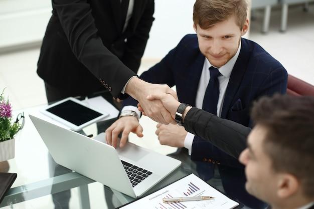 Partnerzy finansowi uścisk dłoni przy biurku w biurze.