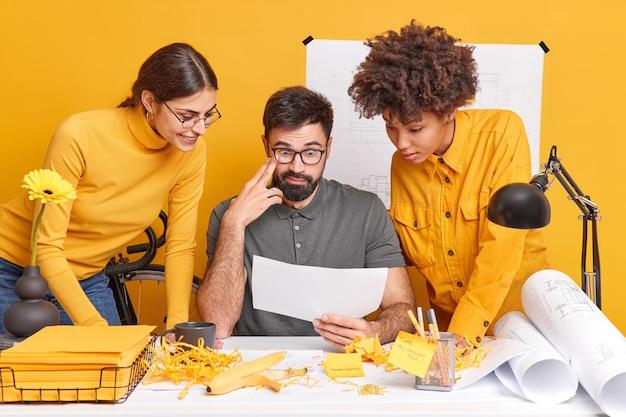 Partnerzy wielokulturowi współpracują przy projekcie projektowym, dyskutują o pomysłach, uważnie przyglądają się ilustracji na papierze, wspólnie przeprowadzają burze mózgów nad szkicami projektowymi w przestrzeni coworkingowej. różnorodni profesjonaliści