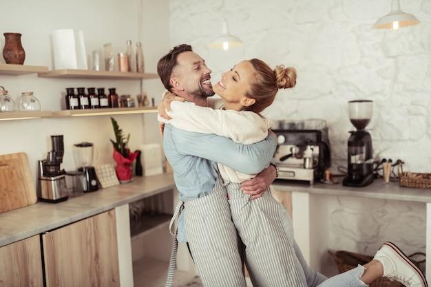 Partnerzy życiowi. szczęśliwa para uśmiechnięta radośnie przytulona do siebie przed sprzętem kuchennym.
