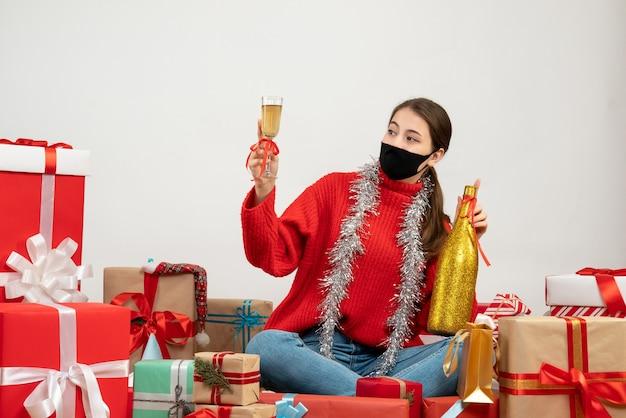 Party girl z czarną maską, trzymając butelkę szampana i opiekania, siedząc wokół prezentów na białym tle