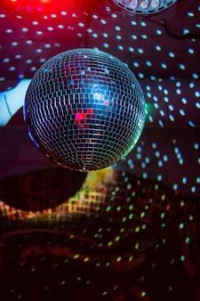 Party lustrzana kula disco odbijająca fioletowe światła.