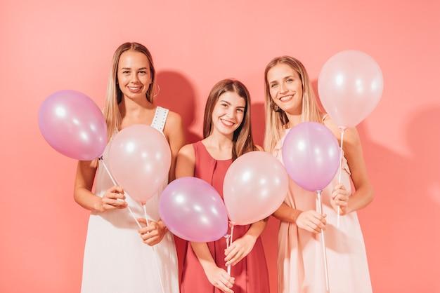 Partyjne dziewczyny pozuje z balonami