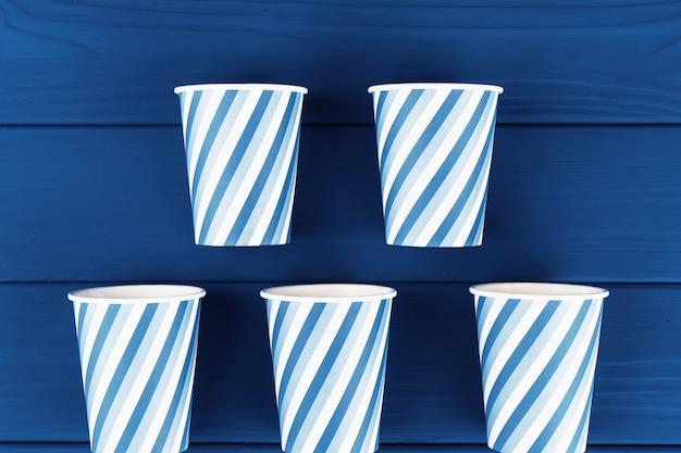 Partyjne filiżanki na błękitnych drewnianych deskach, widok z góry
