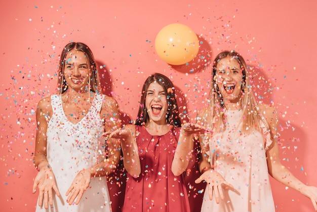 Partyjni przyjaciele pozuje z confetti