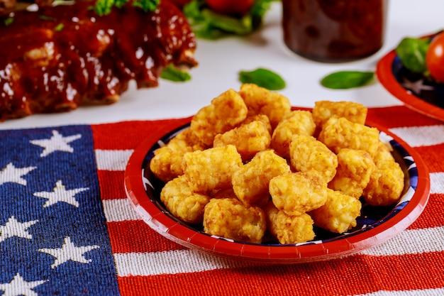 Partyjny stół z jedzeniem i amerykańską flagą.