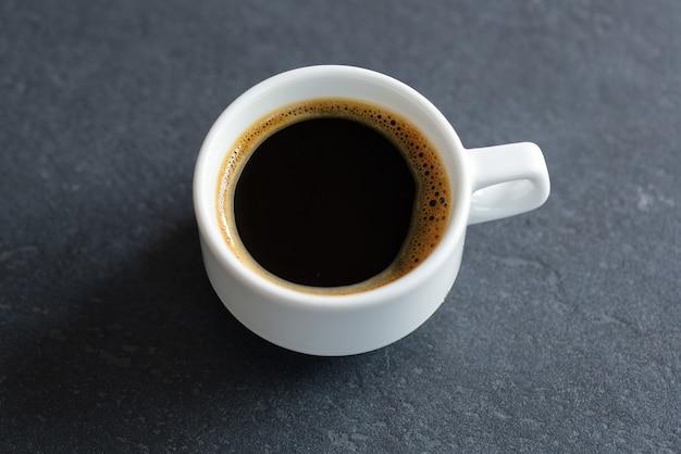 Parująca filiżanka espresso na szarym tle. zbliżenie