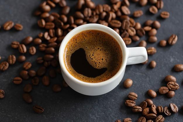 Parująca filiżanka espresso na tle ziaren kawy. zbliżenie
