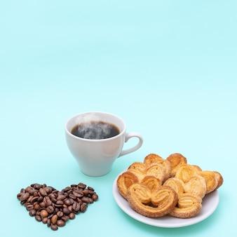 Parująca filiżanka kawy, ciasteczka w kształcie serca, ziarna kawy w kształcie serca na niebieskim tle
