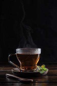 Parujący napar miętowy w szkle kryształowym ze świeżymi liśćmi mięty, na ciemnym rustykalnym drewnianym podłożu.