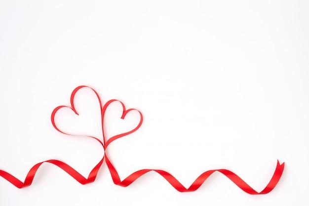 Pary czerwony tasiemkowy serce na białej tła i kopii przestrzeni.