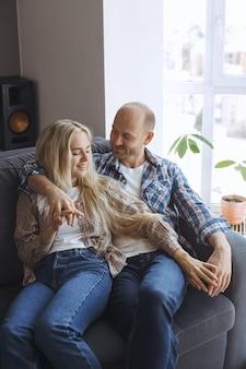 Pary obejmowanie odpoczywa na kanapie w domu
