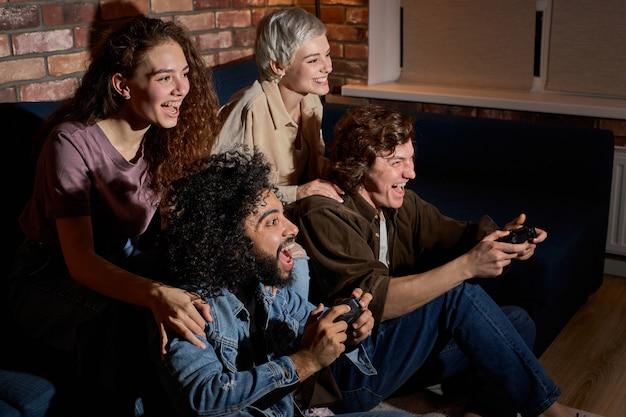 Pary przyjaciół trzymających joystick, grając w gry wideo na konsoli, aby się dobrze bawić, siedząc zrelaksowany. szczęśliwi faceci i panie w strojach codziennych spędzają czas razem