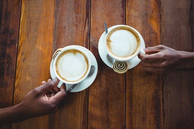 Pary ręka trzyma filiżankę kawy