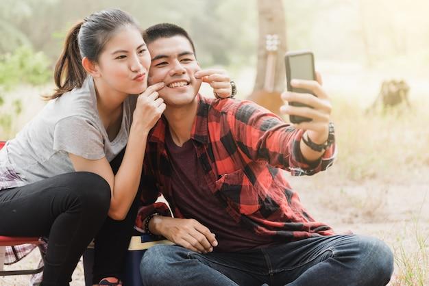 Pary używające smartfonów do robienia selfie
