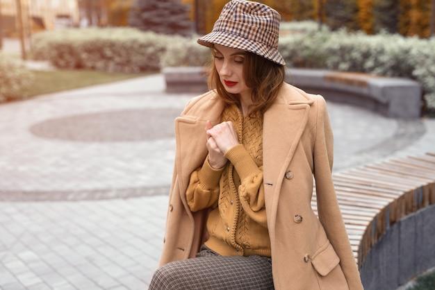 Paryska dziewczyna w beżowym płaszczu i kraciastym kapeluszu panama siedząca na okrągłej ławce czekająca na randkę lub