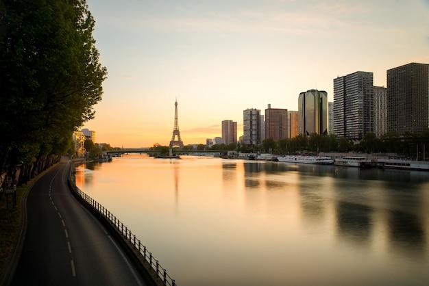 Paryska linia horyzontu z wieżą eifla i wonton rzeką w paryż, francja. piękny wschód słońca w paryż, francja.