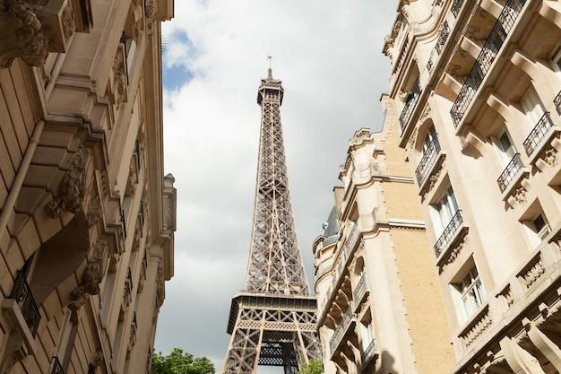 Paryska ulica z widokiem na słynną wieżę eifel w paryżu w pochmurny letni dzień