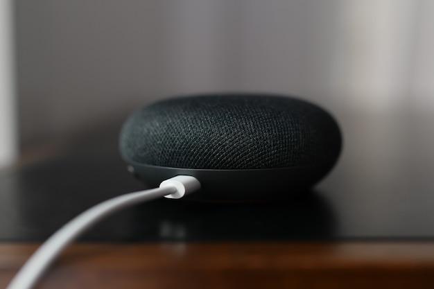 Paryż, francja – 20 września 2021 r.: czarny fizyczny przycisk przełącznika mikrofonu z kablem google home mini