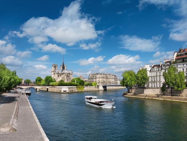 Paryż wiosną. turystyczna łódź na rzece mija ile st louis