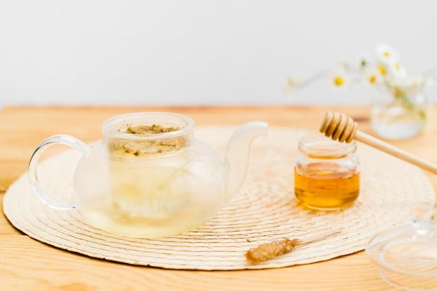 Parzenie herbaty w czajniczku w pobliżu słoika z miodem